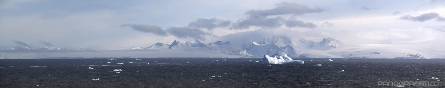 Large Iceberg Drifting in Suspiros Bay - Deeper into the bay icebergs are seen passing in front of a misty mountainous backdrop